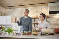 キッチンで部屋でくつろぐ日本人シニア夫婦