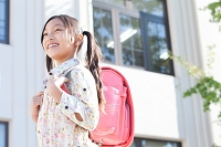 校庭でランドセルを背負っている小学生の日本人の女の子
