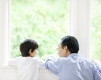 窓辺で見つめ合う祖父と孫