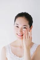 目元にクリームを塗る日本人女性