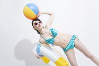 浮輪とビーチボールを持つ水着姿の日本人女性