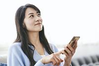 スマートフォンを操作する40代日本人女性