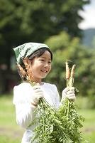 収穫した人参を持つ女の子