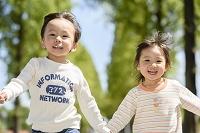 新緑の公園で駆けっこする日本人の子供