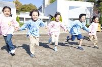 手を繋いで園庭を走る幼稚園児