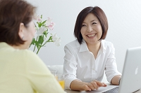 パソコンを見ながら談笑する中年日本人女性