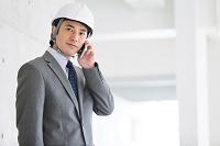 建設現場で電話をする日本人ビジネスマン