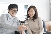 自宅でスマートフォンをみるシニア世代の夫婦
