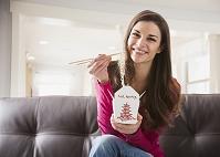 ヌードルを食べる笑顔の女性