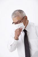マスクをして咳込む中高年日本人男性
