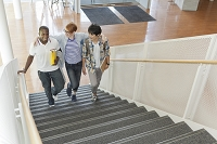肩を組んで階段を上がる留学生と大学生