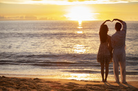 砂浜でハートを作るカップル