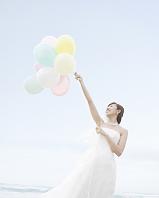 風船を持って海辺に立つ新婦