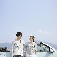 車の前で見つめ合うカップル