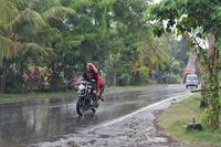 インドネシア スコールの中バイクに乗る男性