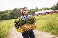 カゴに入っている野菜を持つ外国人女性