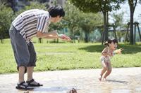 水遊びをする娘と父親