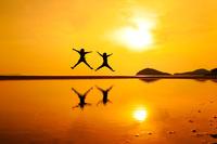 香川県 夕暮れの父母ヶ浜でジャンプする観光客