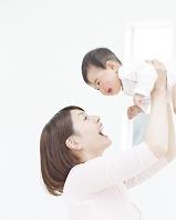 赤ちゃんを抱きあげる母親