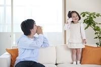 糸電話をする父と娘