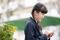 スマートフォンを操作する女子学生