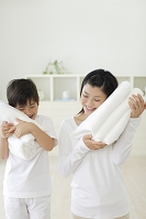 まっ白なタオルを頬にあてる男の子とお母さん