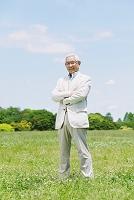 新緑と腕を組むシニアの日本人男性