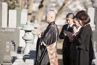 お墓の前で手を合わせる僧侶と喪服姿の遺族