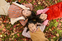 落ち葉の上で寝そべる日本人の子供達