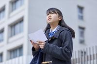 受験票を持って結果を見つめる女子中学生