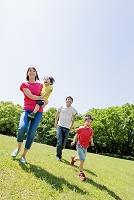 新緑の公園を歩く日本人家族