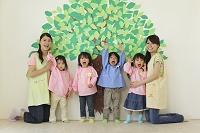 木の壁面の前に立つ幼稚園児と先生