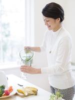 コップに野菜ジュースを入れる日本人女性