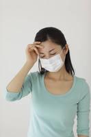 マスクをしておでこに手を当てている女性