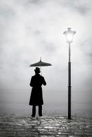 傘をさして佇む男性