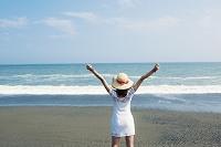 海辺でポーズをとる女性の後ろ姿