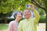 公園でデジタルカメラで撮影する老夫婦