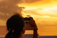 小笠原丸から夕焼けを撮る女性