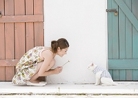 ネコと向かい合う若い女性