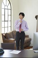 ネクタイを締めながら広いオフィスを歩く日本人ビジネスマン