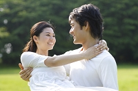 緑の中で男性に抱きかかえられる日本人女性