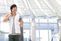 スマホと買い物袋を持って歩く日本人男性