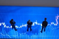 株価グラフとミニチュア人形