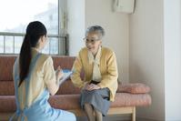 ホームヘルパーの問診を受けるシニアの日本人女性
