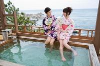 露天風呂で足湯を楽しむ浴衣の日本人女性