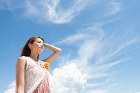 青空の下で遠くを眺めている日本人女性