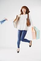 買い物袋を持ってジャンプする日本人女性