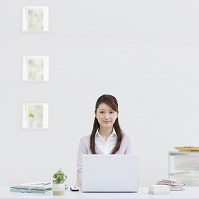 ノートパソコンの前に座る女性