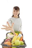 ショッピングカートを押し商品に手を伸ばす若い女性