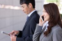 タブレットを操作するビジネスマンと通話中のビジネスウーマン